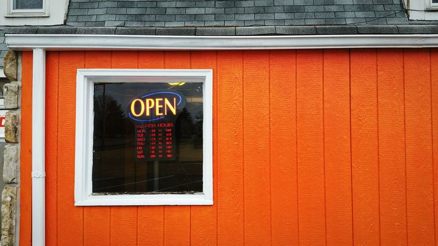 Close-up of open sign on orange wall of shop
