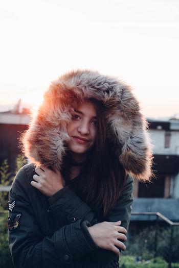 Portrait of teenage girl wearing fur coat against sky