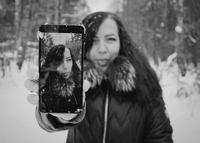 Portrait of woman holding camera outdoors