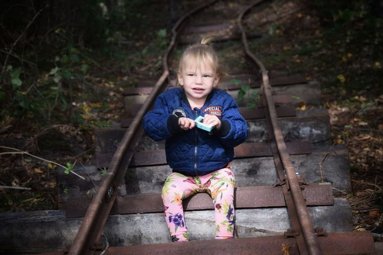 High angle view of cute baby girl sitting on railroad track