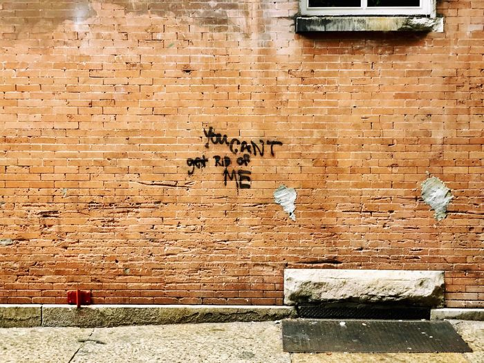 You can't get rid of me Sidewalk Street Wall - Building Feature Day Built Structure Architecture No People Building Exterior Wall Brick Text Brick Wall Graffiti Outdoors Old Brown Textured  Building