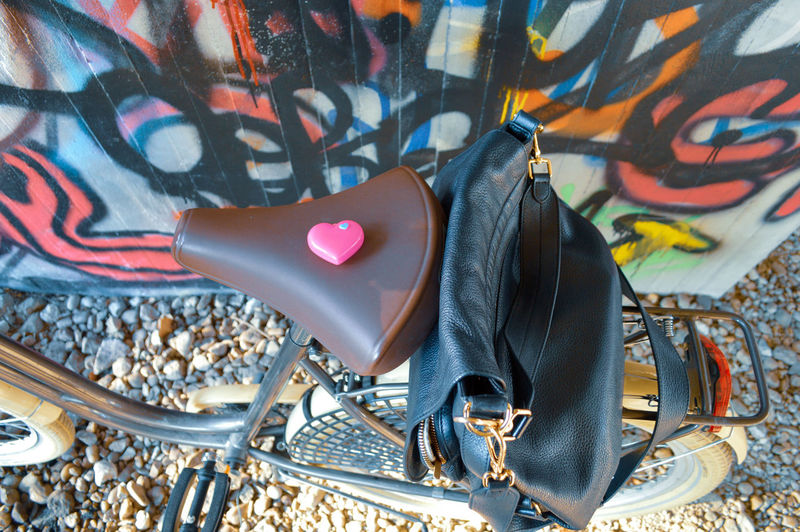 Directly above shot of bag on bicycle against graffiti wall