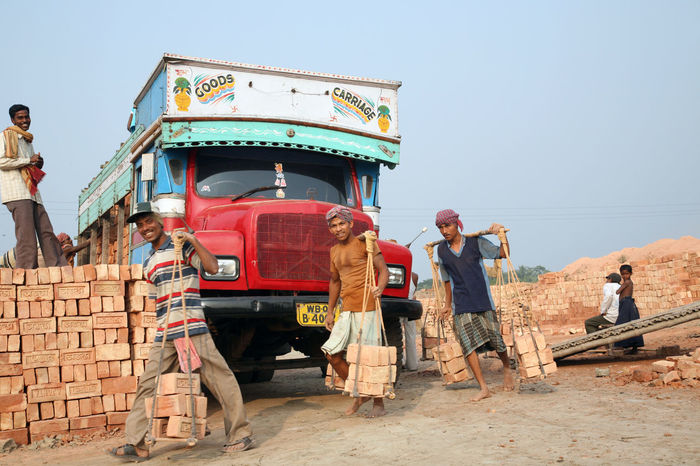 Brick field workers carrying complete finish brick from the kiln, and loaded it onto a truck on January 16, 2009 in Sarberia, West Bengal, India. ASIA Brick Carry Economy Environment Field India Industry Manufacturing Men Rural Sarberia Technology Transportation Truck Vehicle West Bengal Work Worker