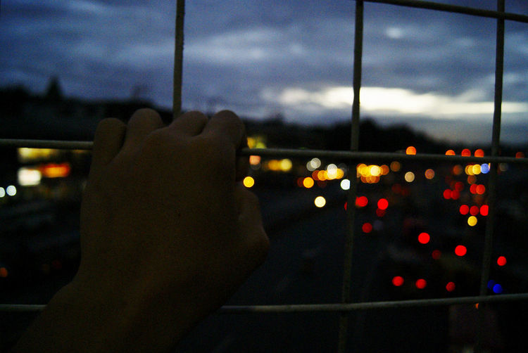 Close-up of hand against illuminated window at night