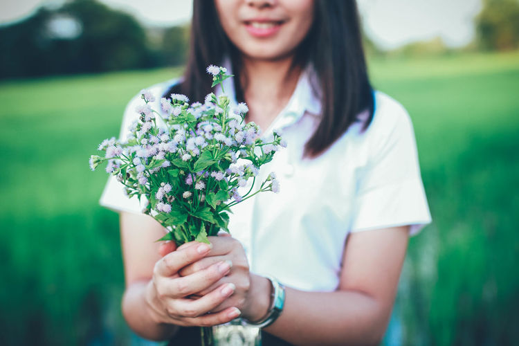 Adult Beautiful Woman Casual Clothing Day Flower Flowering Plant Focus On Foreground Freshness Front View Green Color Hair Hairstyle Hand Holding Leisure Activity Lifestyles Nature One Person Outdoors Plant Real People Women Young Adult Young Women