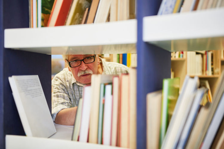 Man by books in shelves
