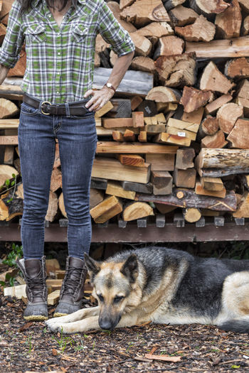 A woman stands in front of her woodpile with her dog after chopping wood. Jeans Rustic Woman Authentic Boot Brown Cabin Casual Clothing Day Flannel German Shepherd Hand On Hip Minimalism One Person Outdoors People Real People Rustic Style Simple Simplicity Standing Strong Woman Timber Wood - Material Woodpile