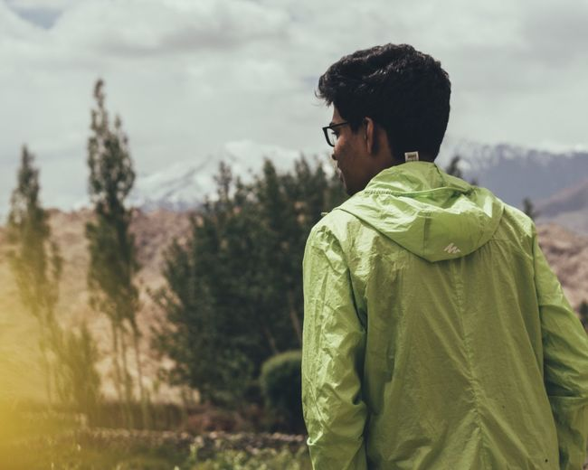 Full length of young man looking at mountains against sky