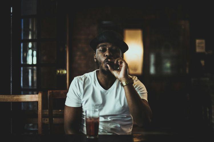 Young man smoking cigar while sitting on table at bar