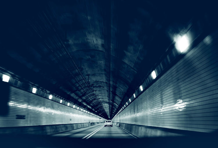 Low angle view of illuminated tunnel at night