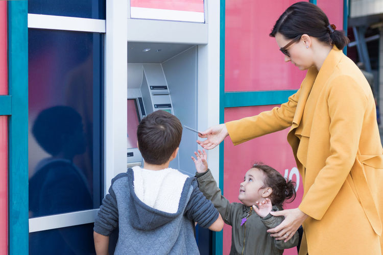 Woman Using Atm While Standing With Children In City