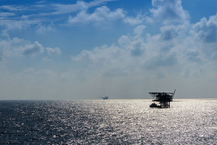 Silhouette oil drill amidst sea against sky