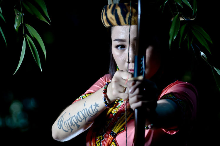 Portrait of young woman holding longbow outdoors