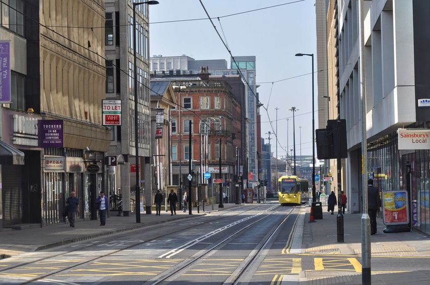 Streets of Manchester. Battle Of The Cities Architecture Building Exterior Built Structure City Street Transportation Car City Street Mode Of Transport City Life EyeEm Gallery Tram EyeEm City Life City Streets  Getty X EyeEm City People On The Street Office Building Outdoors Sky EyeEm Masterclass Commercial Sign City Street