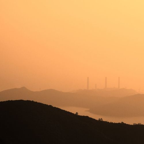 Silhouette smoke emitting from factory against orange sky