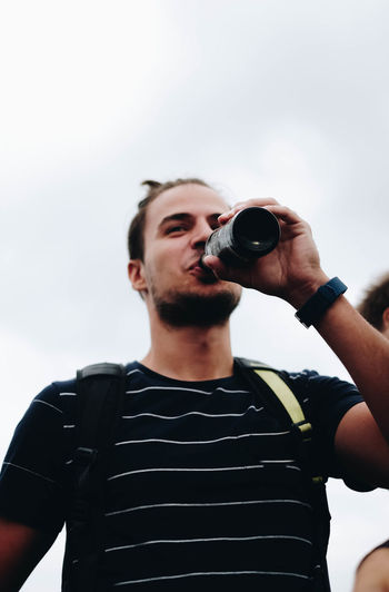 EyeEmOnABoat Alcohol Bottle Casual Clothing Day Drink Drinking Focus On Foreground Food And Drink Front View Holding Leisure Activity Lifestyles Low Angle View Men One Person Real People Refreshment Sky Standing Waist Up