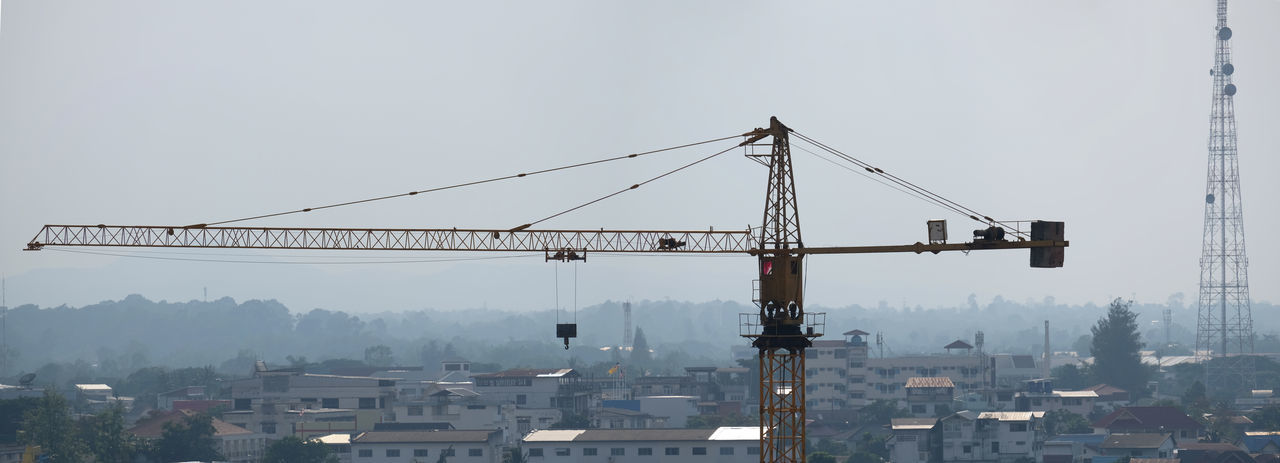 Cranes and buildings against sky