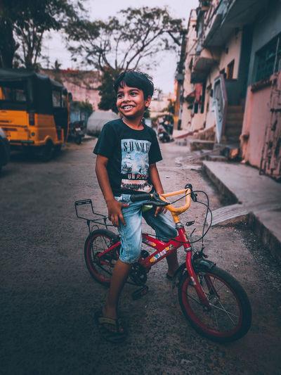 Full length of smiling boy on street in city