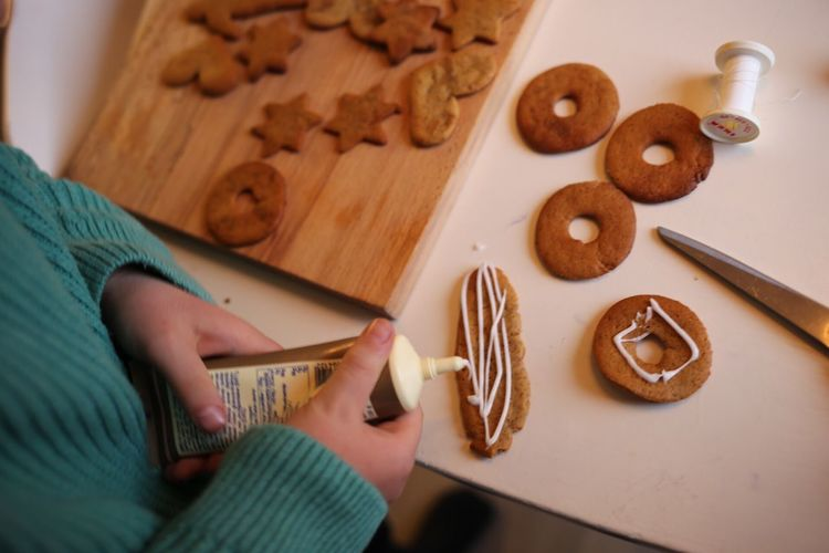 Midsection of girl decorating gingerbread cookies at table