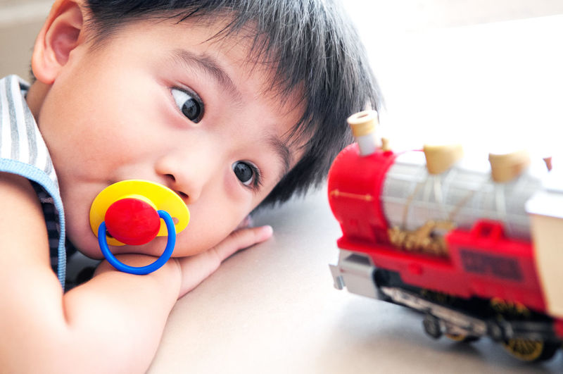 Closeup portrait of a young boy with pacifier and looking at toy train 3 Years Old Mesmerized Natural Light Toy Train Child Childhood Close-up Day Expression Headshot Indoors  Looking Lying On The Floor One Person Pacifier Playing Portrait Toy Young Boy Young Kid