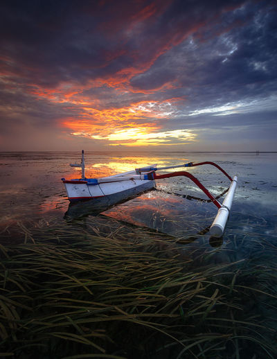 Boat moored on shore against sky during sunset