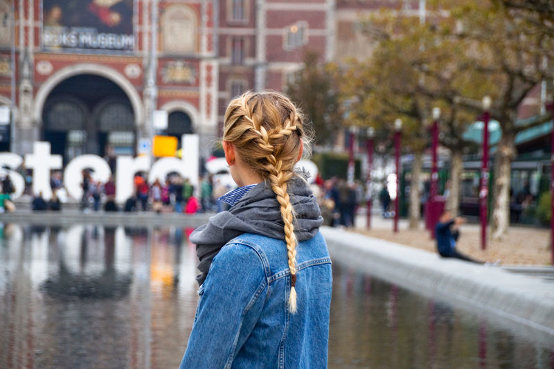 Rear view of woman with braided hair while standing in city
