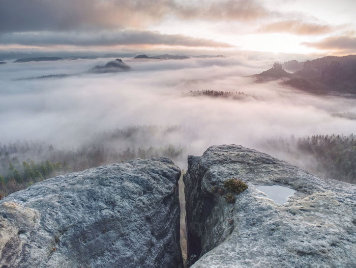 Broken rocks and crags in the nature park in saxony. misty vewpoint with hill and peak in distance