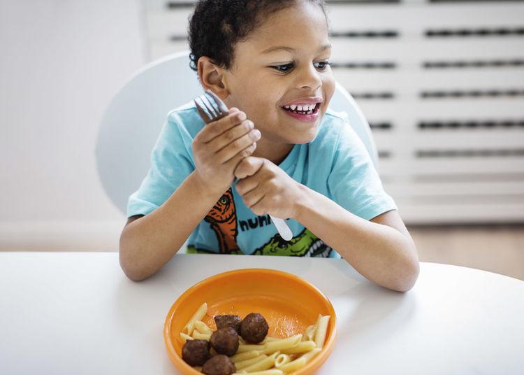 Portrait of happy boy sitting on table