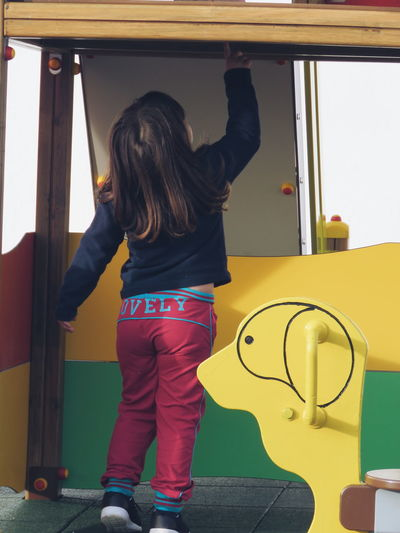 Rear view of girl standing by play equipment