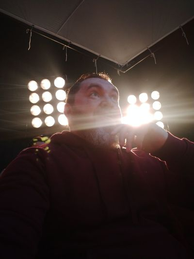 Low angle view of man against illuminated ceiling