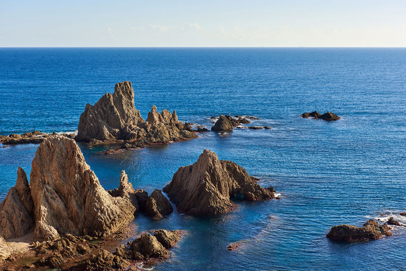 Scenic view of rock formations by sea at cabo de gata-nijar natural park during sunset