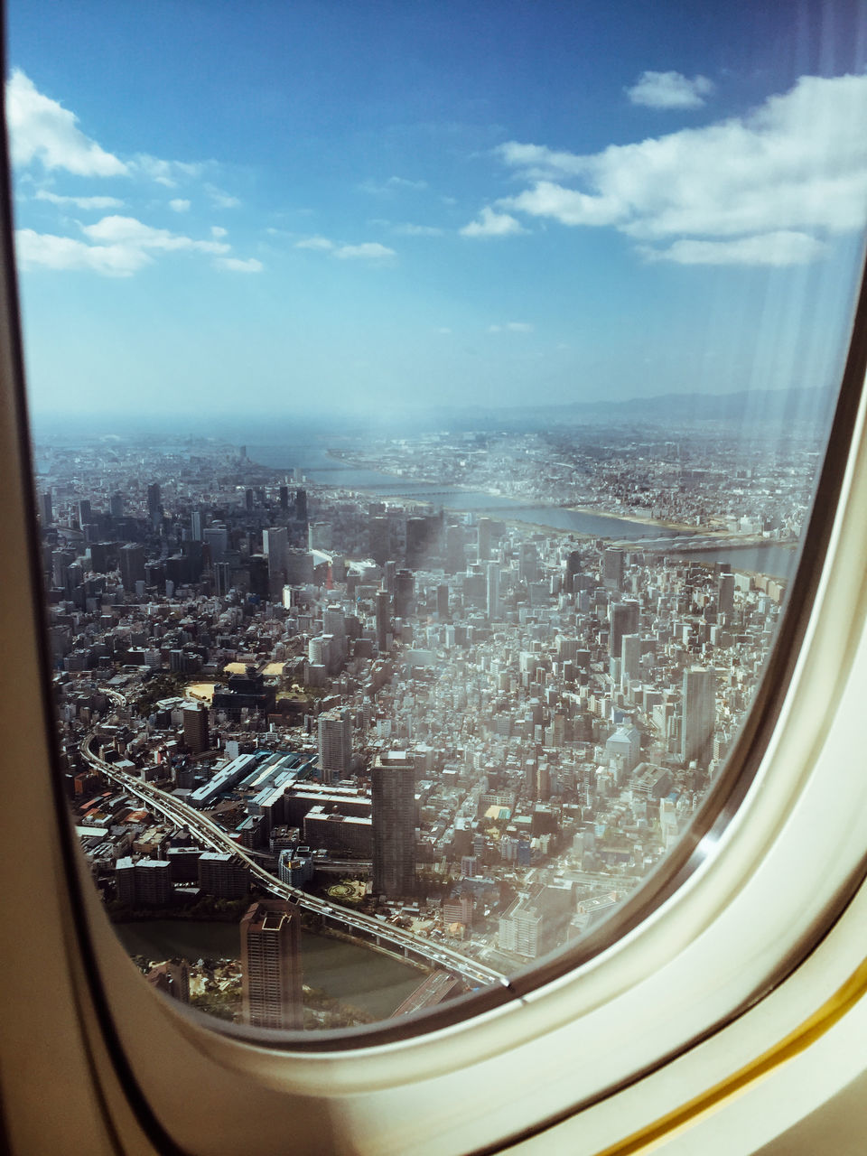 cityscape, city, architecture, aerial view, sky, crowded, building exterior, built structure, transportation, landscape, cloud - sky, skyscraper, outdoors, airplane, day, airplane wing