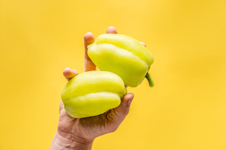 Close-up of hand holding apple against yellow background