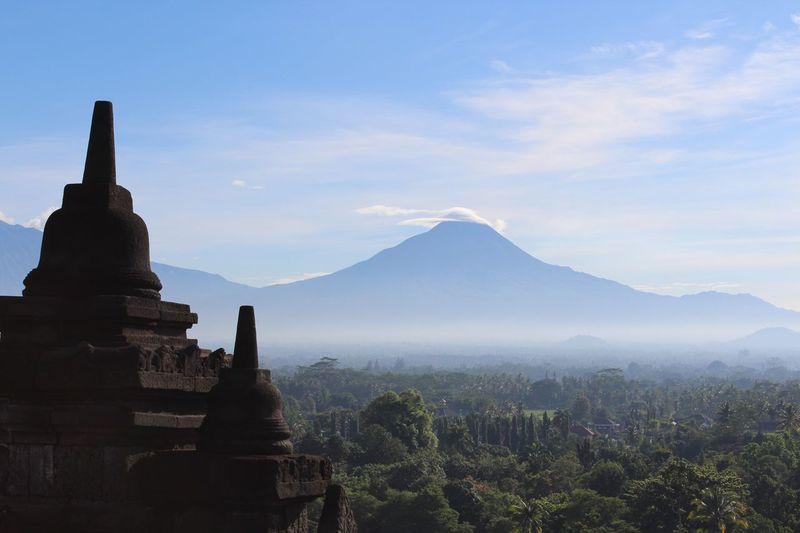 Stupas at borobudur temple against mountains and sky on sunny day