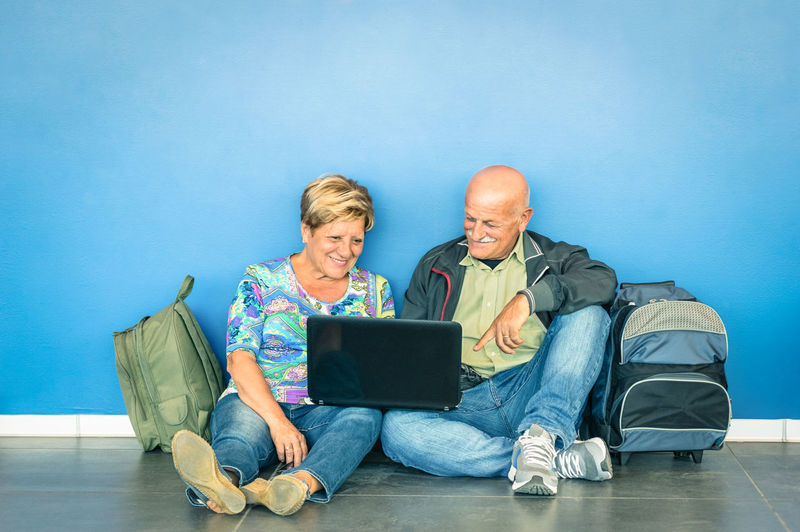 Senior Couple Using Laptop While Sitting Against Blue Wall
