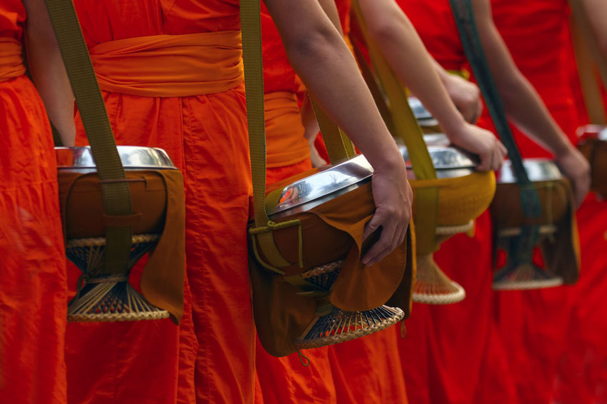 A lot of monk with alms bowl at morning time ,the people put food offerings into a Buddhist monk's bowl,Luang Prabang ,Laos world Culture Heritage Site. Monk  Buddhist Morning Queue WeAreJux World Heritage Site. Alms Bowl Blur Background Body Part Clothes Culture Hand Laos Laos Travel Line Up Luang Prabang Monk's Bowl Offerings Orange Color People Receive Food Time Traditional Yellow Yellow Robe