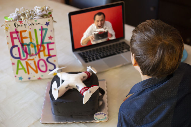 Rear view of man using laptop on table at home