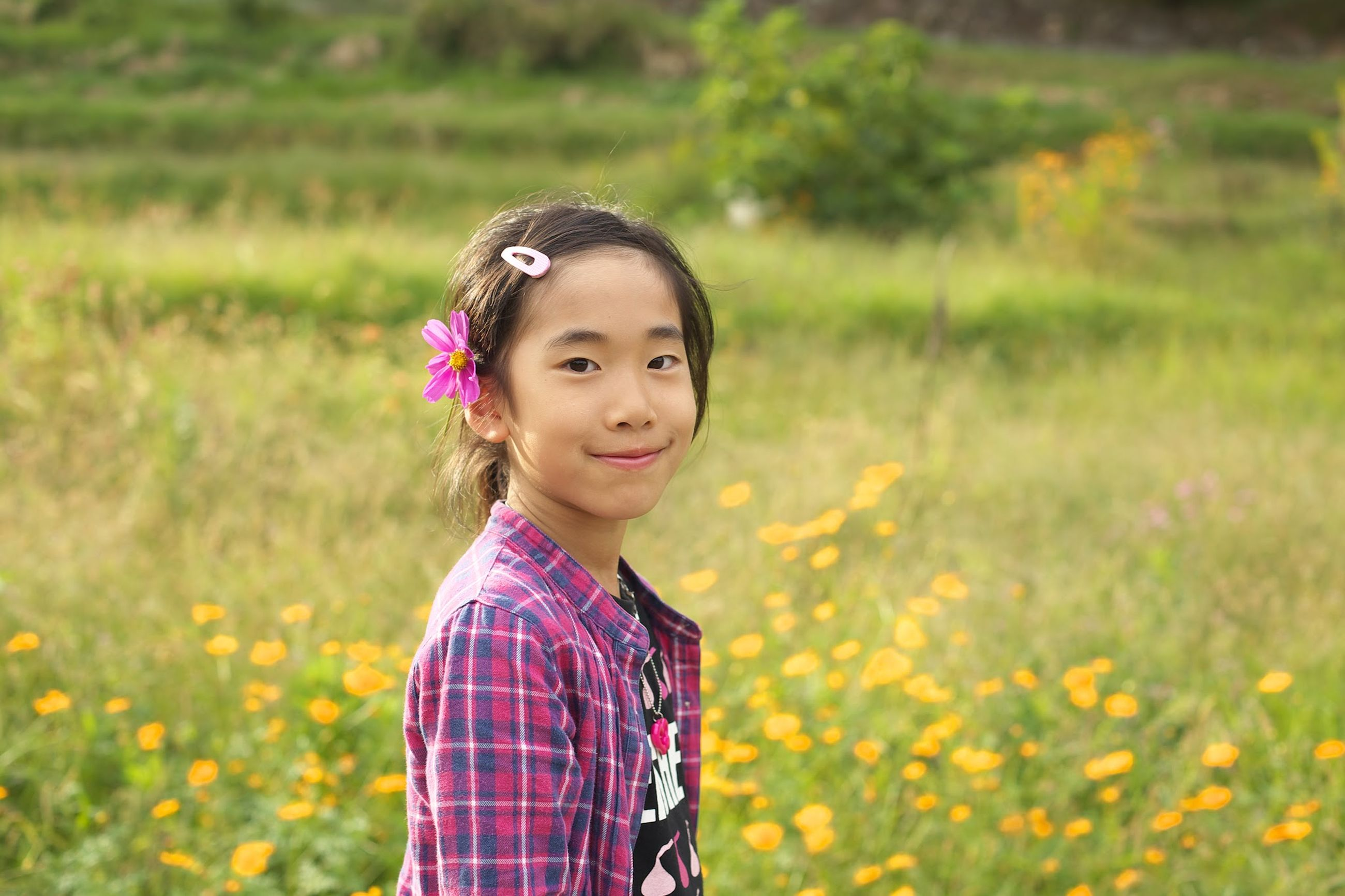 person, looking at camera, portrait, field, elementary age, grass, childhood, lifestyles, leisure activity, smiling, casual clothing, girls, focus on foreground, happiness, innocence, front view, waist up, cute
