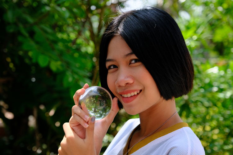 Portrait of smiling young woman holding crystal ball at forest