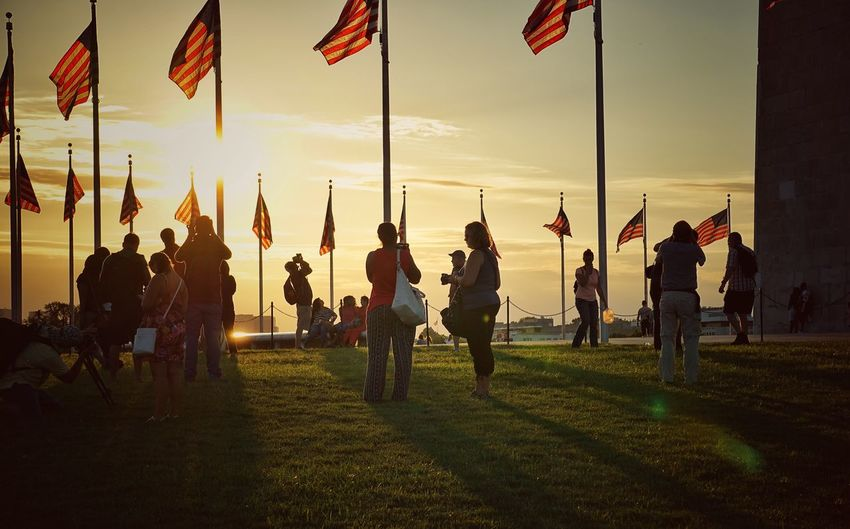 People and american flags on field at washington monument during sunset