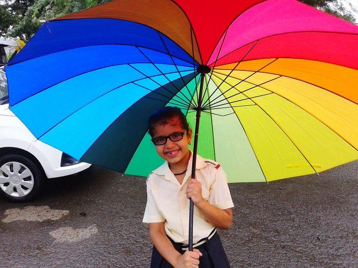 Portrait of smiling girl holding colorful umbrella
