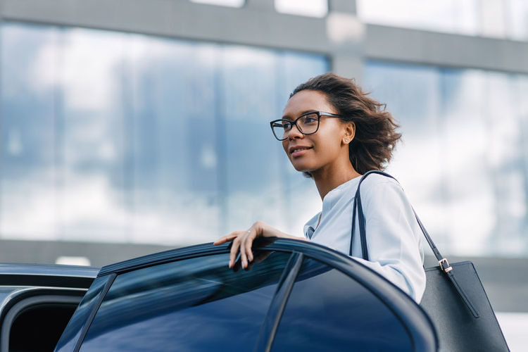 Smiling young woman looking away while standing by car