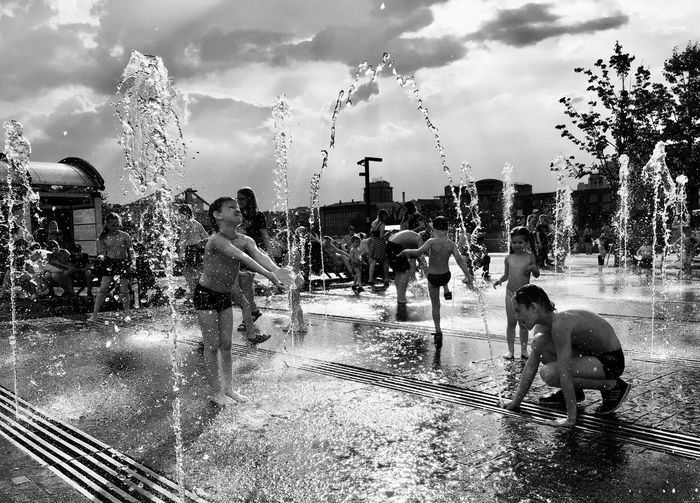 People on wet fountain against sky