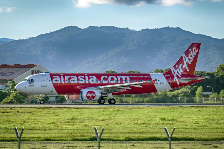 A320 accelerating for takeoff! Air Asia Airbus Airbus A320 Airfield Airplane Airport Grass Kota Kinabalu Airport Malaysia Mountain Panning Sabah Borneo Sky