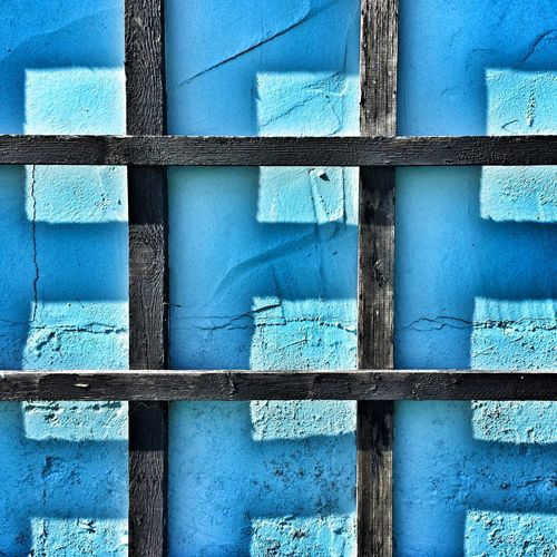 Wooden structure against blue wall