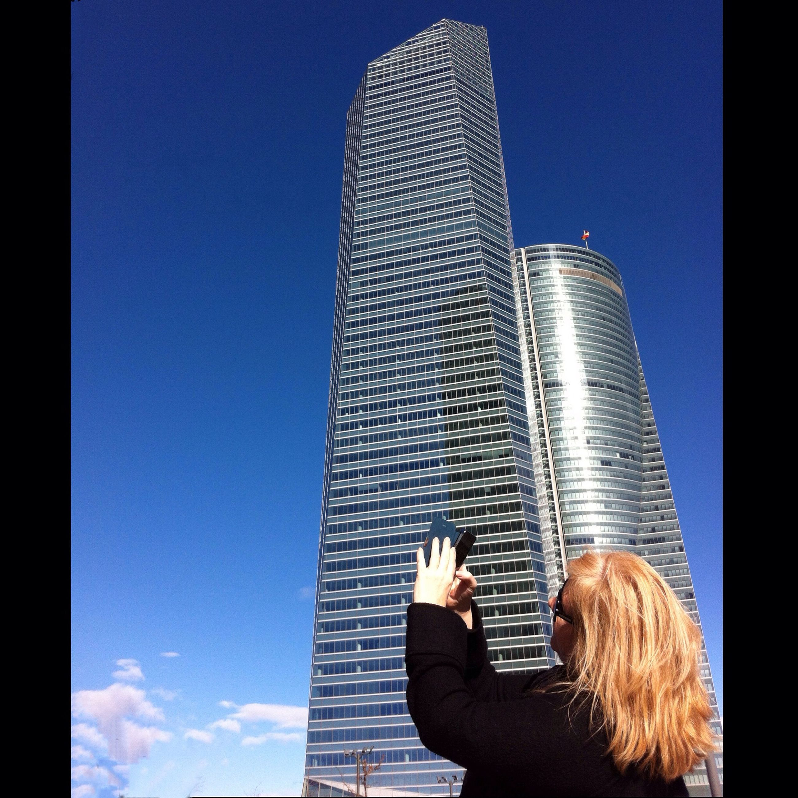 lifestyles, architecture, leisure activity, built structure, skyscraper, modern, building exterior, city, person, waist up, clear sky, tall - high, sitting, office building, men, sunlight, low angle view, indoors