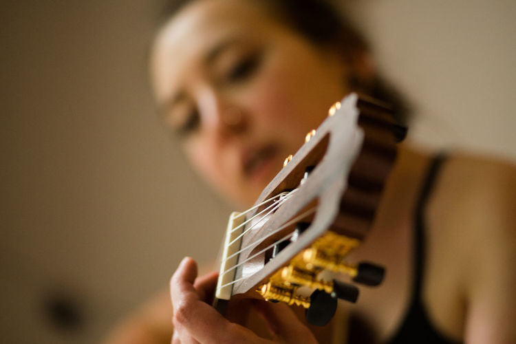 Woman playing the guitar Singing Woman Adult Arts Culture And Entertainment Bokeh Close-up depth of field Girl Guitar Guitarist Headshot Holding Indoors  Leisure Activity Lifestyles Music Musical Instrument One Person Playing Portrait Real People Selective Focus String Instrument Young Adult