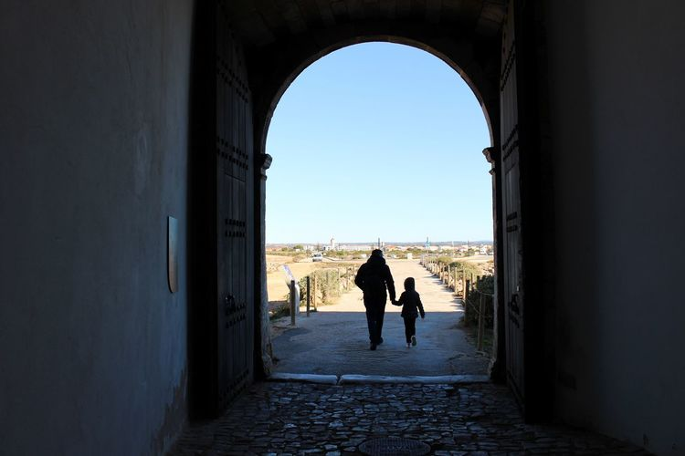 Silhouette people walking in corridor of historic building