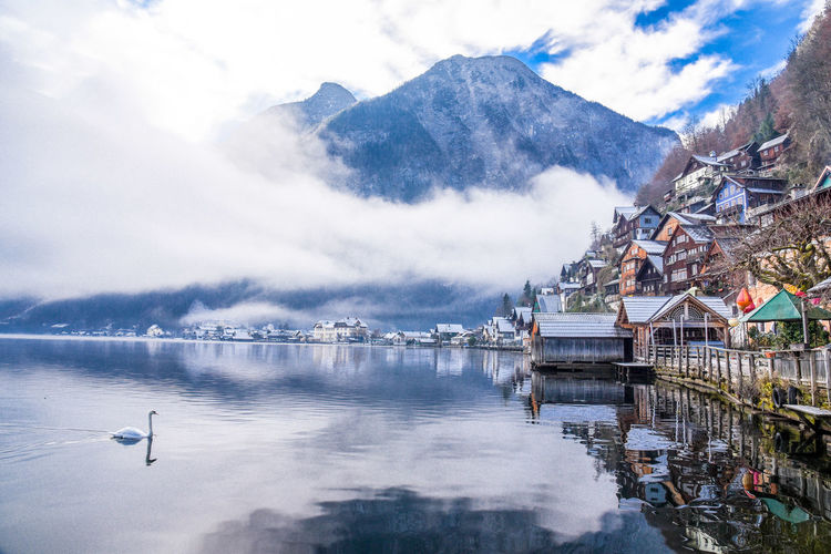 Houses by lake with mountains in background against cloudy sky