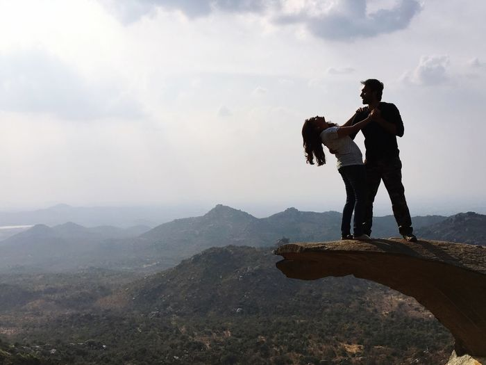 Young Couple Dancing On Mountain Peak Against Scenic Landscape